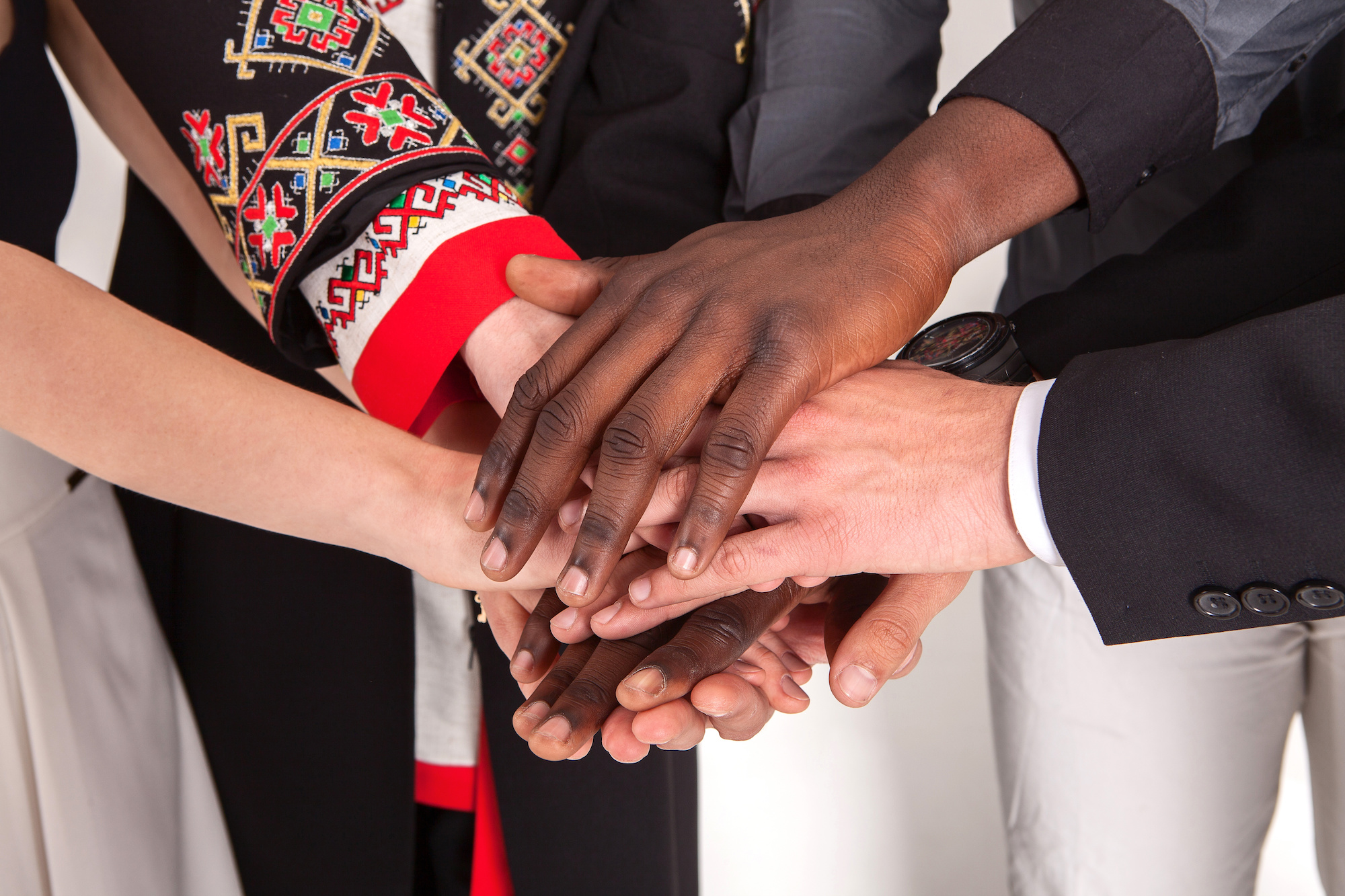 People of different nationalities and religions hold hands. The concept of friendship among peoples. Business concept of team building and partnerships.