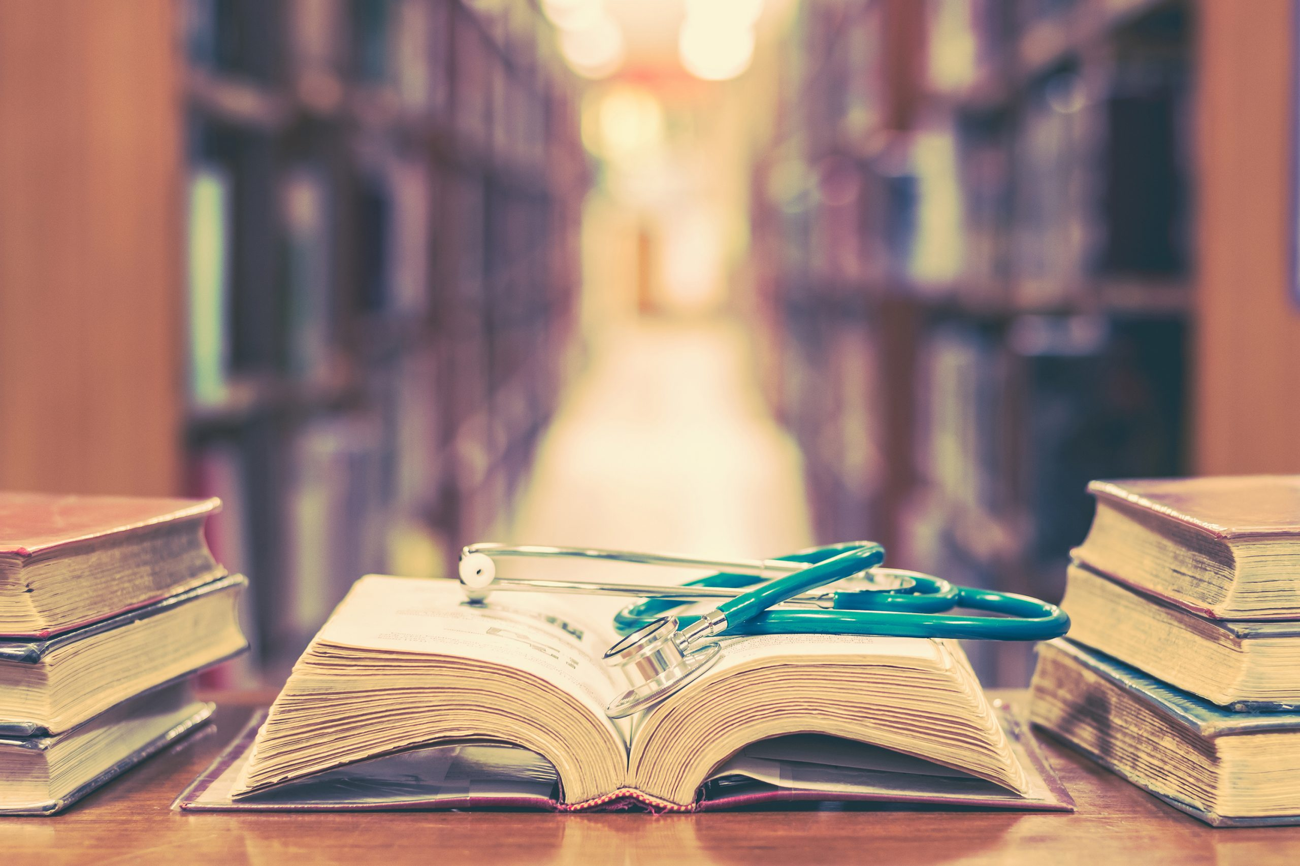 Old book in library with stethoscope on open textbook, stack piles of texts on reading desk, and aisle of bookshelves in  study class room background for medical school education learning concept